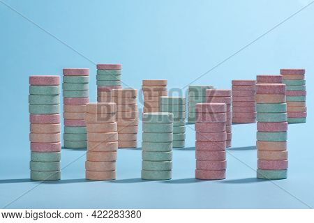 Army Of Columns Of Colourful Pink, Orange And Cyan Tablets Placed On A Light Blue Background