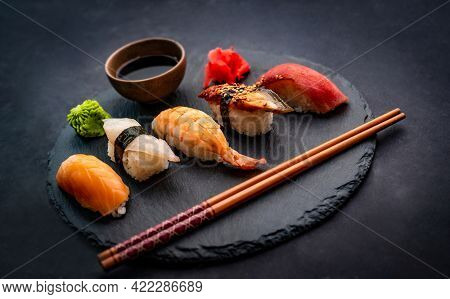 Beautifil composition of sushi sashimi set with shrimps, ginger and soy sauce served with chopsticks and green wasabi on black round plate. Traditional japanese food with rice and seafood