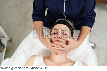 Top View Of Beautician Doing Facial Anti-aging Lifting Massage On Woman Face At Spa Clinic. Lymphati