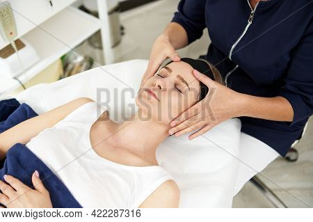 Beautician Doing Facial Anti-aging Lifting Massage On Woman Face At Spa Clinic. Professional Lymphat