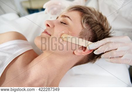 Closeup Of Beautician Hand Using Wooden Spatula For Applying Transparent Anaesthetic Gel On Woman's