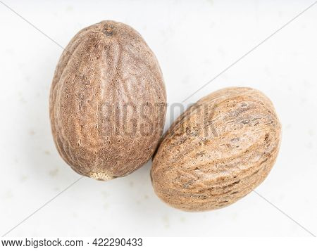 Top View Of Two Whole Nutmeg Fruits On Gray Ceramic Plate
