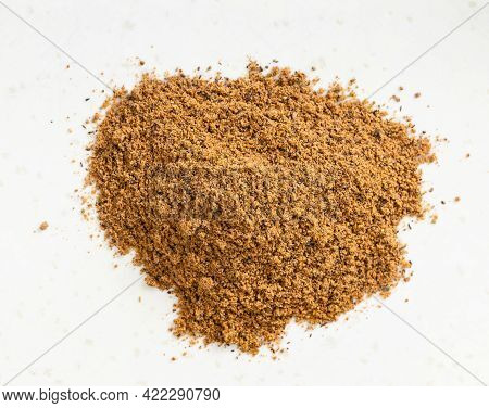 Top View Of Pile Of Nutmeg Powder Close Up On Gray Ceramic Plate