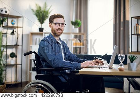Side View Of Bearded Young Man Sitting In Wheelchair And Typing On Wireless Laptop. Handsome Disable
