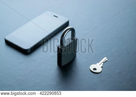 Business Security Protection. Modern Space Grey Mobile Phone With Padlock, Key On Dark Background. S