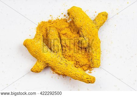 Top View Of Pile Of Turmeric (curcuma) Powder And Roots Close Up On Gray Ceramic Plate