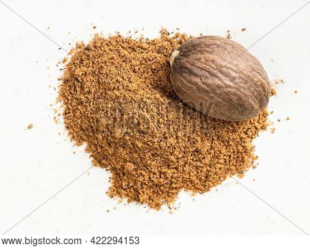 Top View Of Nutmeg Seed And Powder Close Up On Gray Ceramic Plate