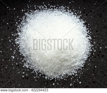 Above View Of Pile Of White Refined Beet Sugar Close Up On Black Ceramic Plate
