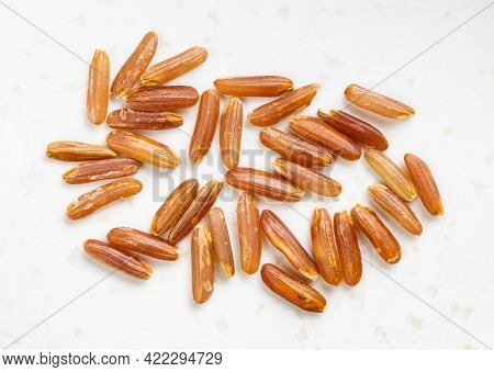 Several Raw Red Rice Grains Close Up On Gray Ceramic Plate