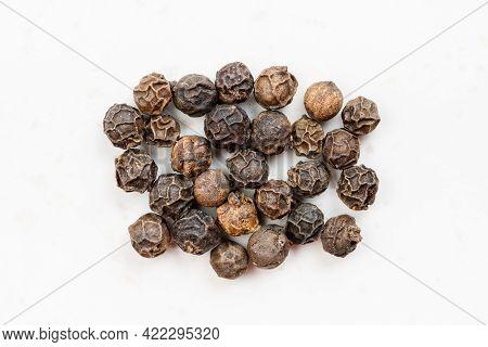 Several Hainan Black Peppercorns Close Up On Gray Ceramic Plate