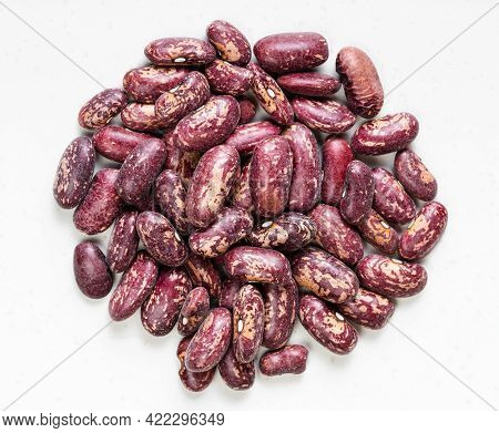 Top View Of Pile Of Raw Red Spotted Pinto Beans Close Up On Gray Ceramic Plate