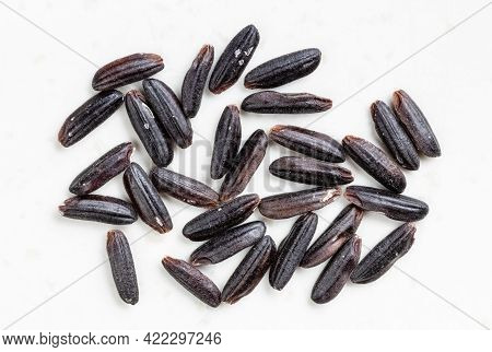 Several Raw Black Rice Grains Close Up On Gray Ceramic Plate