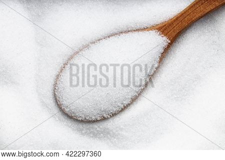 Top View Of Wood Spoon With Sugar Substitute - Crystalline Extract Of Stevia Plant Close Up On Pile