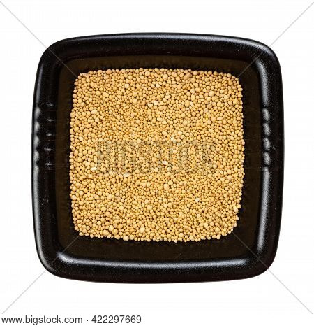 Top View Of Granulated Dried Yeast In Black Bowl Isolated On White Background