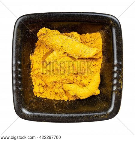Top View Of Turmeric (curcuma) Powder And Roots In Black Bowl Isolated On White Background