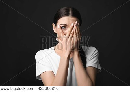 Young Woman Feeling Fear On Black Background