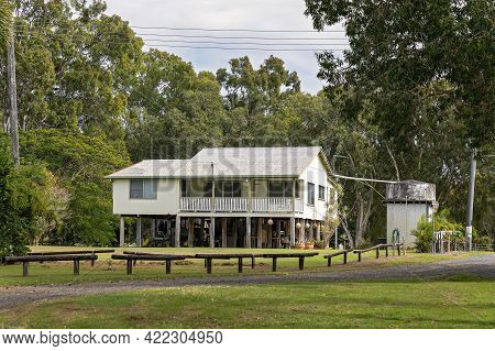 Mackay, Queensland, Australia - May 2021: An Older Style High Beach House In A Tree Filled Oceanside