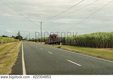 Mackay, Queensland, Australia - May 2021: Farmer Driving A Combine Harvester Along The Side Of The R