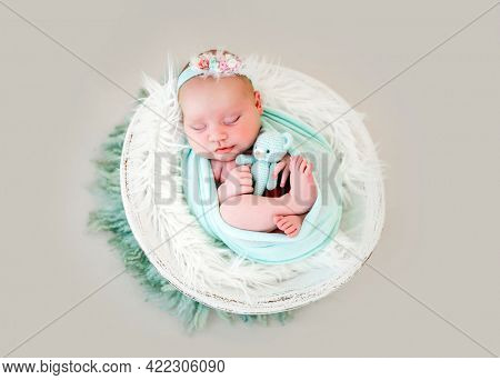 Adorable newborn baby girl lying on her back in the cocoon in white basin, sleeping and holding knitted teddy bear in her hands. Sweet infant child napping with toy during studio photoshoot
