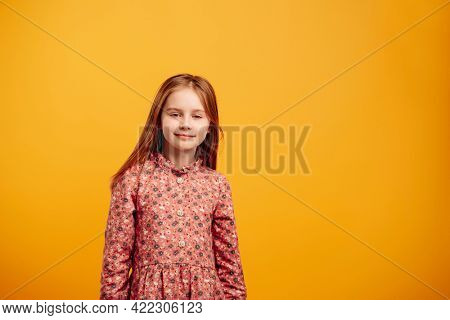 Portrait of little girl wearing beautiful dress isolated on yellow background with copyspace. Pretty female kid looing at the camera and smiling