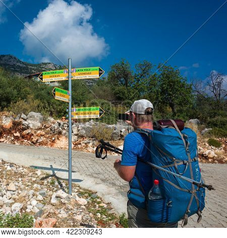 Lycian way, Turkey - 21 October, 2019: Sign pointers on Lycian way hiking trail, Man with backpack taking photo of direction arrows