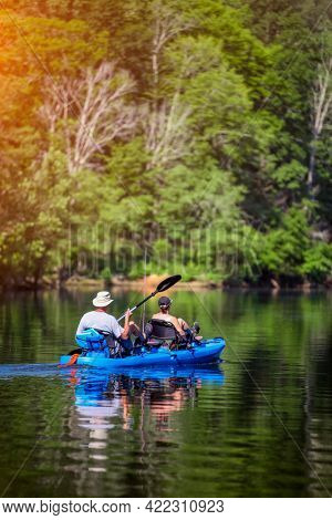 Two unidentifiable people in a canoe kayak on a beautiful lake in North Carolina