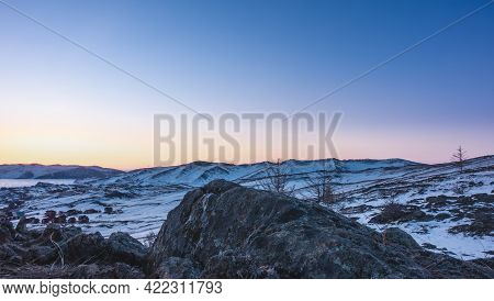 Dawn Over The Snowy Hills. The Sky Over The Ridge Is Pink And Yellow. Rural Houses And Sparse Vegeta