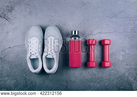 Top View Of White Sport Shoes Sneakers, Glass Water Bottle And Pink Dumbbells On Marble Grey Backgro