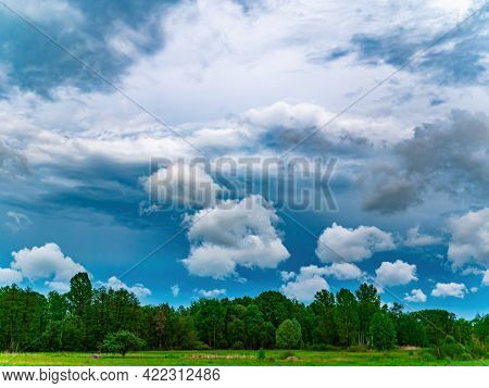 Thunderous Sky With White Clouds Over Green Trees Of Deciduous Forest.