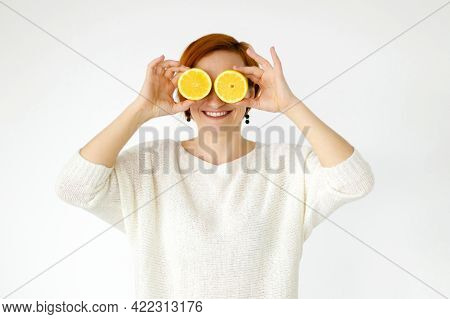 Red Haired Woman Smiles With Snow White Smile And Covered Her Eyes With Lemons. Strange Face. Grimac