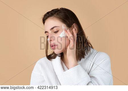 Woman Beauty Face, Portrait Of Beautiful Female Model Applying Moisturizer Cream On Her Pretty Face.