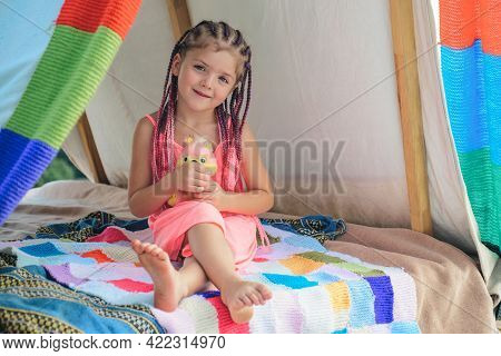 Smiling Kid With Dreadlocks In Tent. Girl Playing In Tent. Child Camping. Having Fun Outdoors At Cam