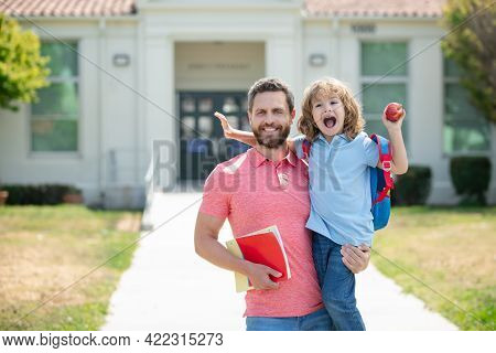 Father And Son Walking Trough School Park. Parent Leads A Little Child School Boy In First Grade.