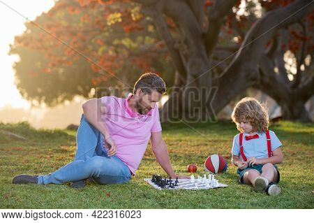 Father And Son Playing Chess Spending Time Together In Park. Kids Chess School.