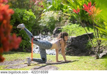 Fitness Woman Doing Stretching Exercise Outdoor In Park. Fit Body On Nature. Athletic Girl Doing Kic