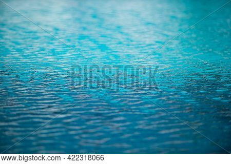 Blue Pool Water Background. Blurred Transparent Clear Calm Water Surface Texture. Water Waves In Sun