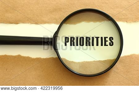 The Magnifying Glass Reveals The Priorities Text Appearing Behind The Torn Brown Paper. Business Con