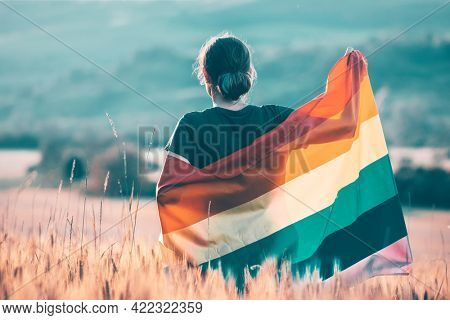 Woman holding a Gay Rainbow Flag over blue summer sky. Bisexual,gay, lesbian, transsexual symbol. Happiness, freedom and love concept for same sex couples