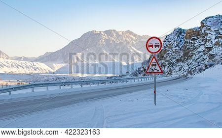 A Road Pole, A Sign Prohibiting Overtaking On The Slippery Icy Road, A Sharp Turn Of The Highway On