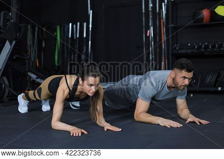 Portrait Of Beautiful Young Sports Couple On A Plank Position.