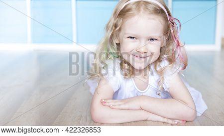 Curly Blonde Girl Lies On The Wooden Floor. Concept Childrens Room Warm Floor. Banner