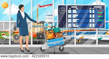 Woman And Hand Truck Full Of Bags In Terminal Interior. Arrival Departure Board. Airport Luggage Tro