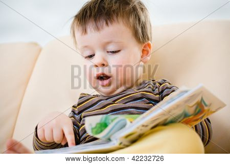 Cute little boy reading book on sofa poster