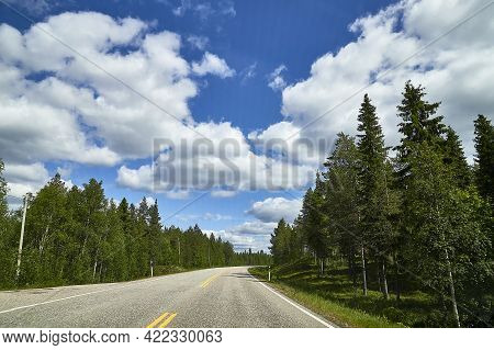View From Relief Car Windscreen On The Blue Sky With White Clouds, Grey Asphalt Road And Landscape W