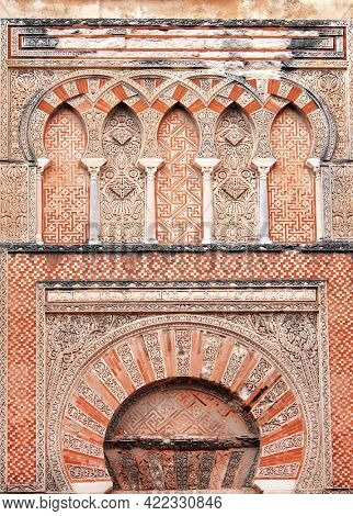 Arch on gate of Mezquita (Great Mosque of Cordoba), Spain, Europe. Ornament in the Moorish style. Text on the wall - quote from the Quran. UNESCO world heritage site