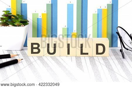 Build Word Written On The Wood Block With Chart, Glasses And Pencils