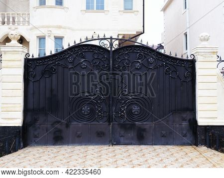 Black Gates With A Wrought-iron Pattern Of Monograms Adjoin The White Columns Of The Fence That Encl