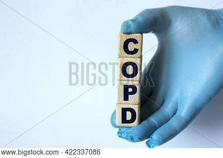 Copd (chronic Obstructive Pulmonary Disease) Is An Acronym On Cubes Held By A Hand In A Blue Glove.