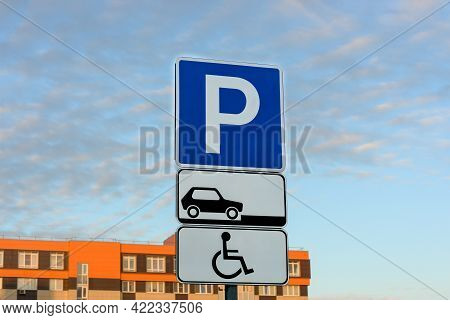 Road Parking Sign On The Background Of City Orange Houses And Blue Sky