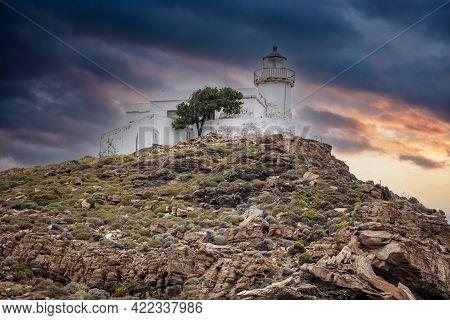 Kea Island, Greece. Lighthhouse Tamelos On A Rocky Cliff, Cloudy Sky Background